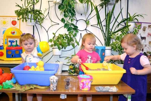 Три девочки играют в контейнерах с песком и водой