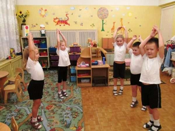 Дети на зарядке тянут ручки вверх