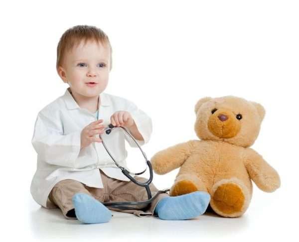 Радостный мальчик со стетоскопом готов лечить плюшевого медведя