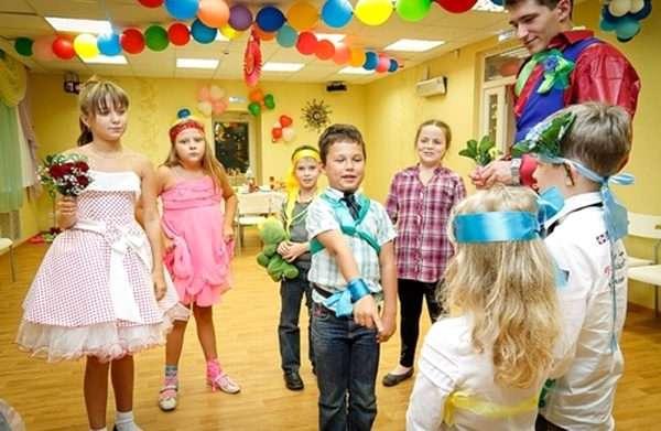 Дети в нарядной одежде стоят в кругу, мальчик выполняет задание