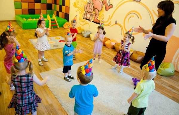 Воспитатель проводит музыкальную игру с младшими дошкольниками, мальчик стоит в центре круга, другие дети хлопают в ладоши