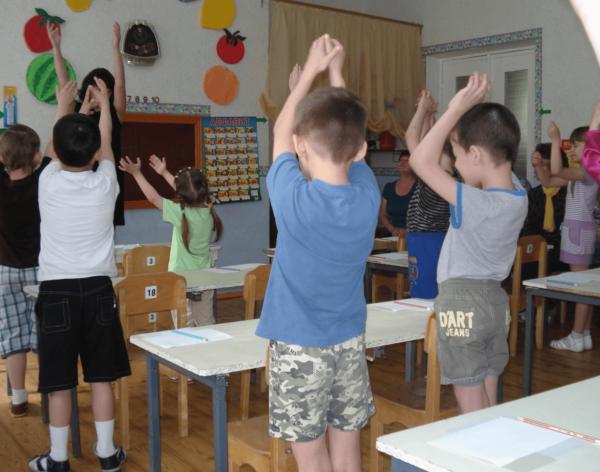 Дети с поднятыми вверх руками делают гимнастику возле парт