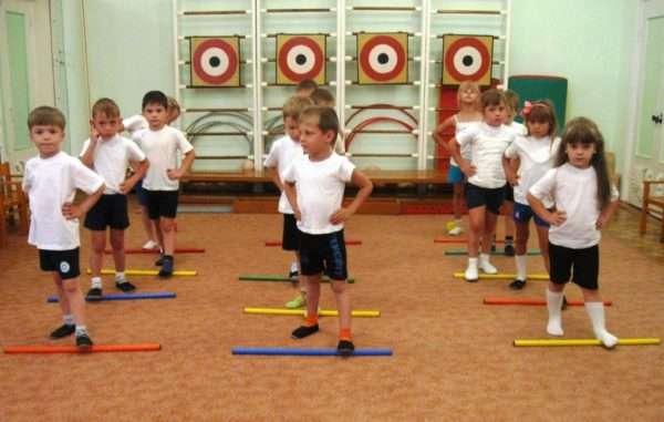 Дети в спортивном зале катают гимнастические палки ногами