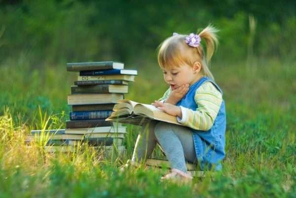 Стопка книг и девочка на полянке читает