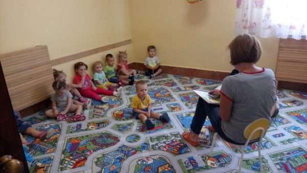 Воспитательница читает книгу детям, сидящим на ковре