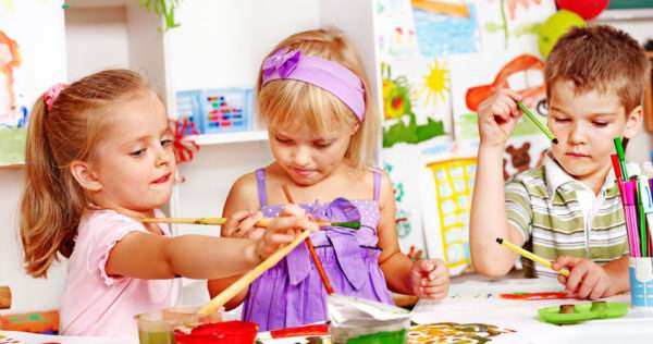 Трое детей рисуют за столом