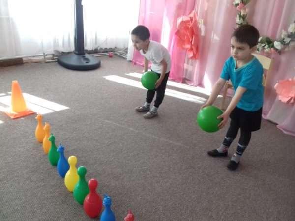 Два мальчика мячами сбивают кегли