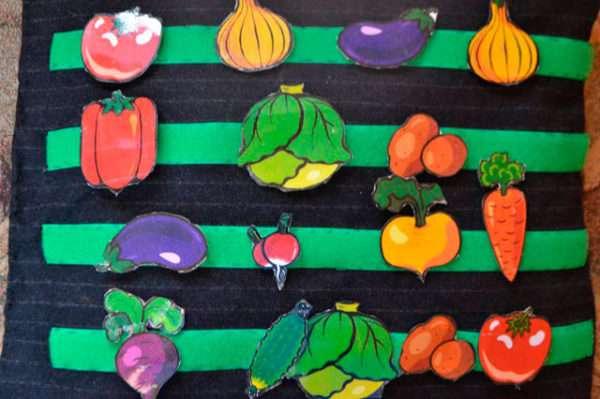 Грядки огорода с фигурками овощей