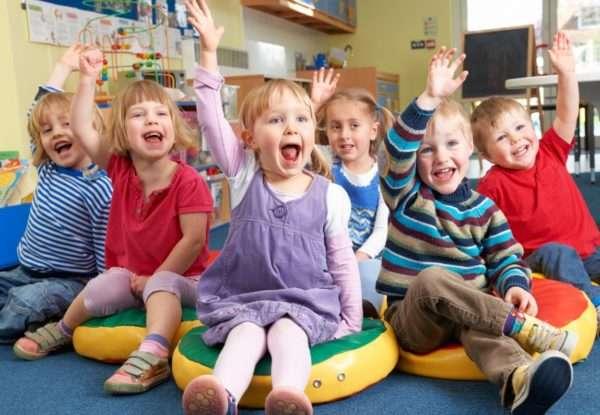 Радостные дети сидят на полу, подняв руку вверх