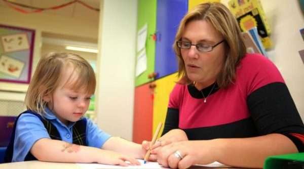 Воспитатель помогает девочке писать ручкой