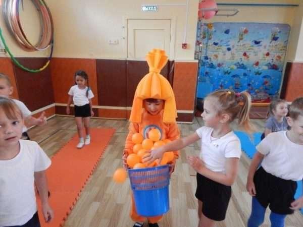 Дети собирают мячики в корзину, которую держит ребёнок в костюме