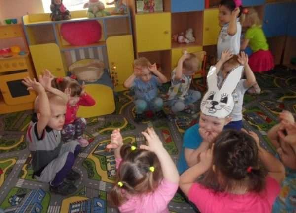 Дети сидят вокруг ребёнка в маске зайчика