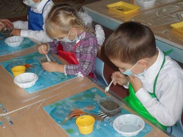 Дети в медицинских масках и фартуках исследуют свойства цемента
