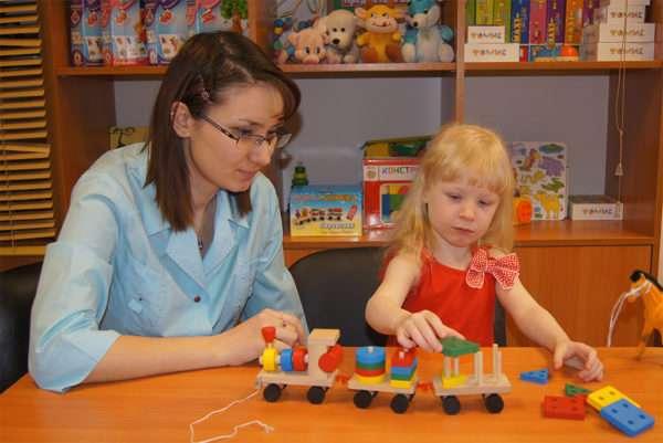 Девочка играет с конструктором, педагог наблюдает