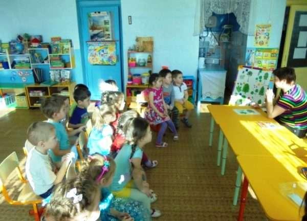 Педагог сидит за столом перед детьми