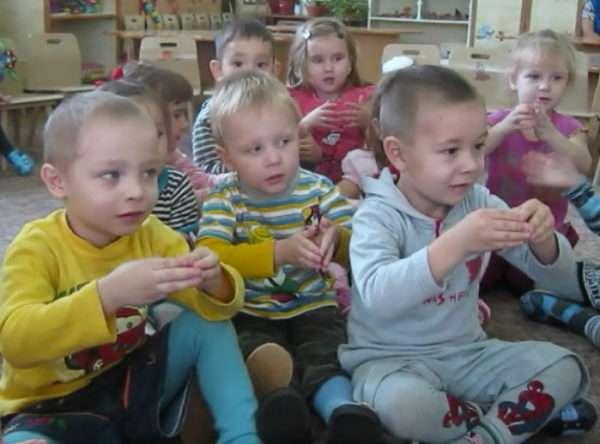 Малыши сидят на коврике и выполняют пальчиковую гимнастику
