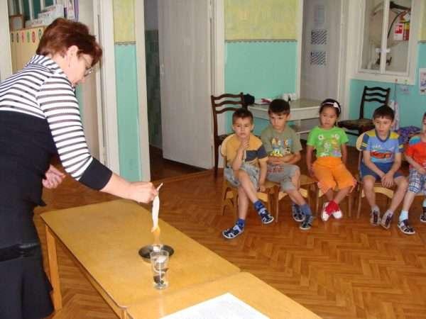 Воспитатель демонстрирует дошкольникам опыт с огнём
