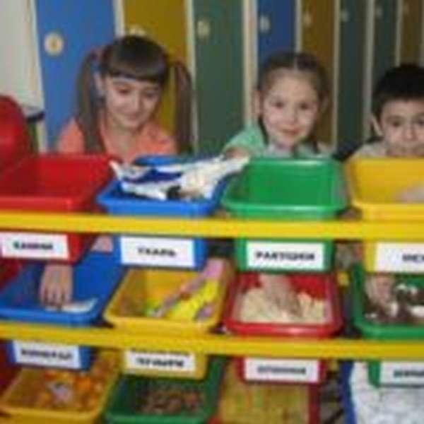 Трое детей стоят рядом со стеллажом с материалами для исследований