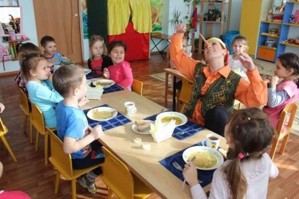 Дети и педагог в костюме Буратино за столом