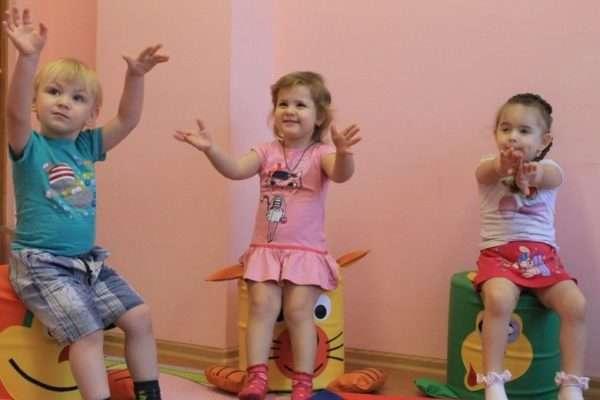 Мальчик и две девочки сидят на мягких пуфиках и крутят фонарики руками
