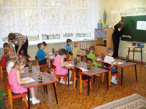 Дети, сидя за партами, рисуют цветными карандашами