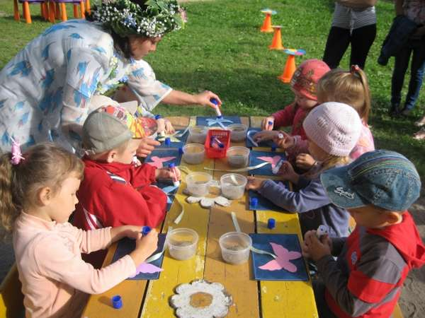 Дети и воспитатель проводят на улице опыты с песком