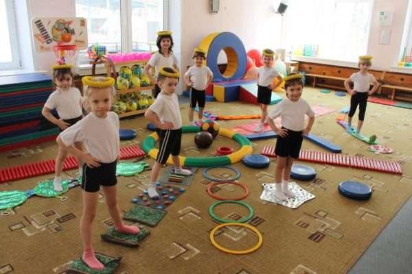 Дети в футболках и шортах стоят в зале, на полу разложено спортивное оборудование