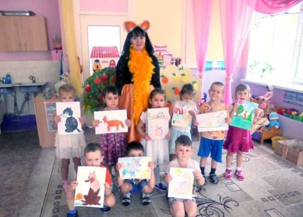 Дети с рисунками в руках и педагог в костюме лисички