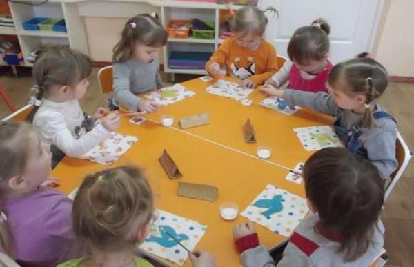 Дети за столом делают аппликацию голубая птица