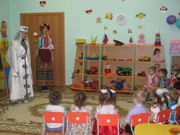 Дети, сидя на стульчиках, смотрят на двух педагогов в национальных костюмах