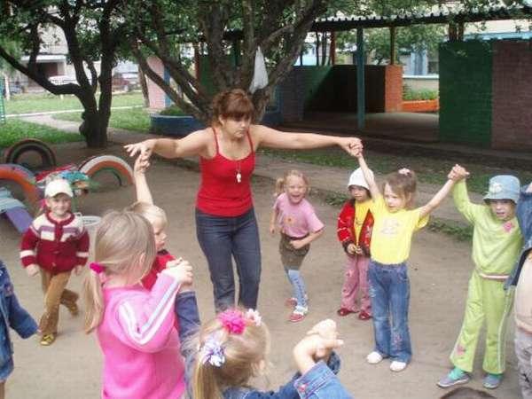 Педагог делает с детьми спортивное упражнение на улице