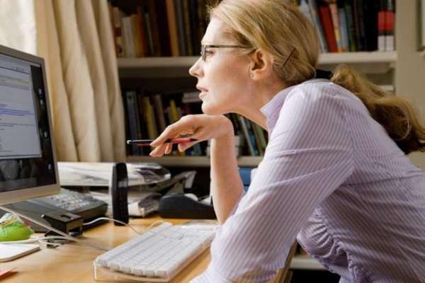 Женщина в очках сидит перед монитором