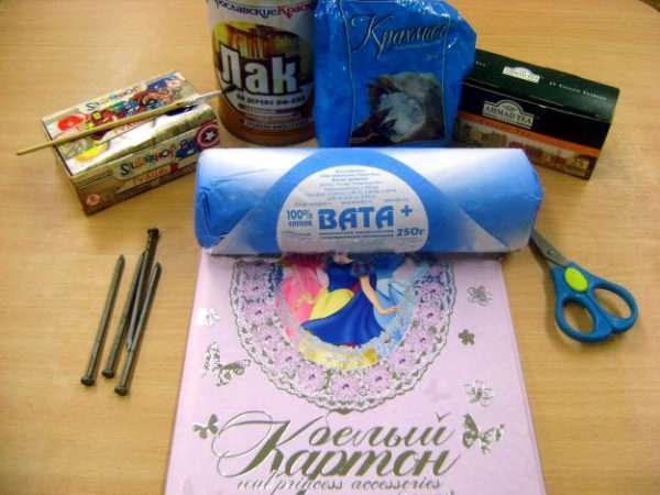 На столе разложены материалы для работы: крахмал, вата, картон, ножницы и т. д