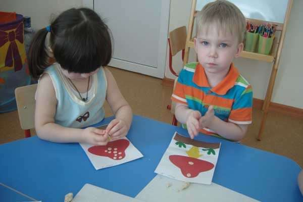 Мальчик и девочка делают аппликации мухоморов