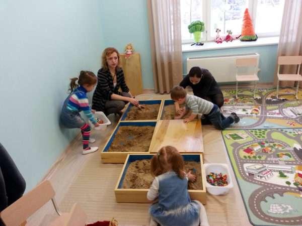 Дети играют в песочном центре в группе, педагоги помогают
