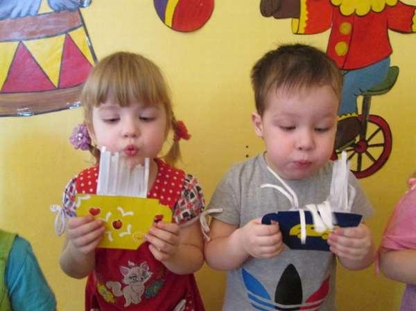 Мальчик и девочка дуют на тренажёры для дыхательной гимнастики