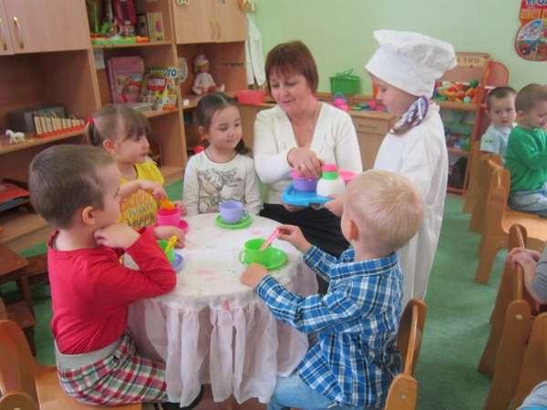дети и воспитатель играют в чаепитие
