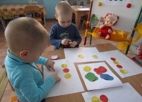 Два мальчика делают аппликацию из кругов цветной бумаги