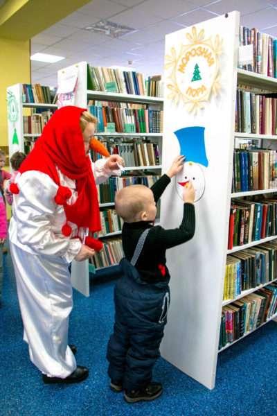 Ребёнок выполняет квест в библиотеке, педагог в костюме снеговика стоит рядом