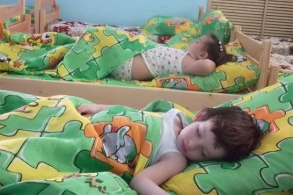 Ребёнок спит в кроватке под одеялом в зелёном пододеяльнике