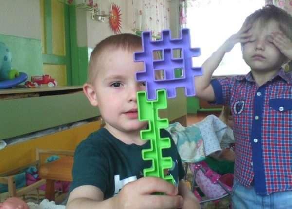 Мальчик держит сложенные детали конструктора, на заднем фоне другой мальчик закрыл глаза руками