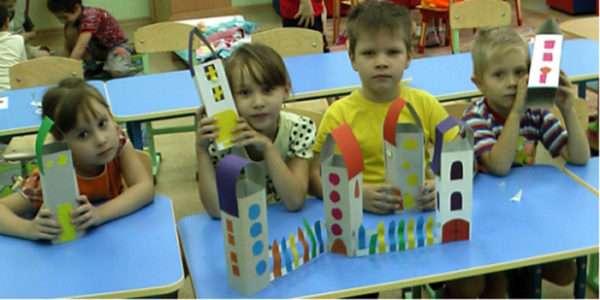 Ребята, сидя за партами, держат в руках самостоятельно изготовленные домики из бумаги