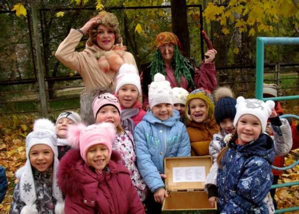 Улыбающиеся дети и педагоги в костюмах стоят у раскрытого сундука