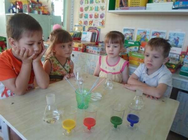 Четверо детей сидят за столом, на котором расставлено оборудование для опытов с водой
