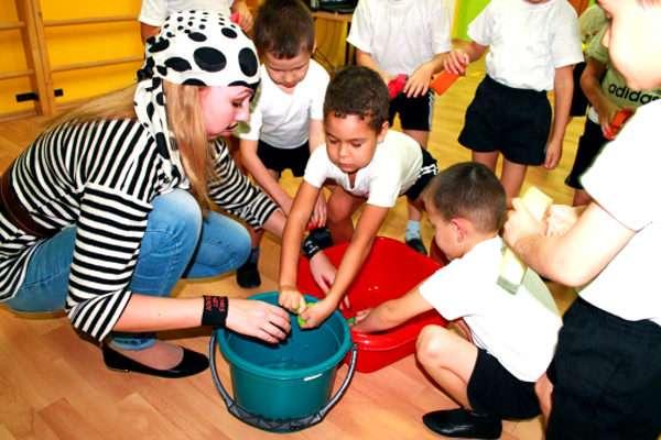 Дети переносят воду с помощью губки