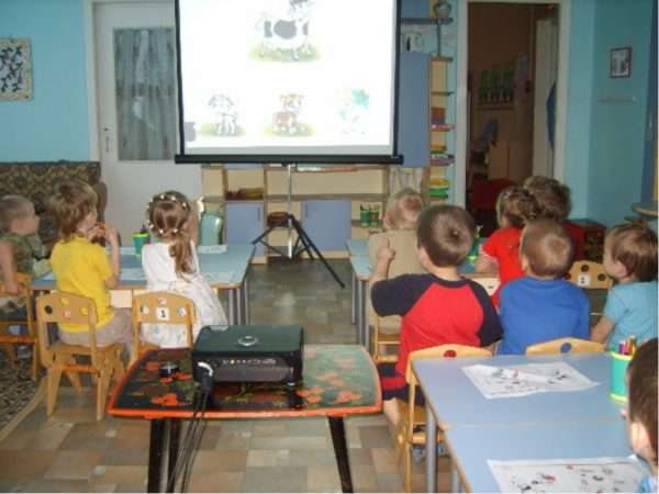 Дети рассматривают картинки на мультимедийном экране