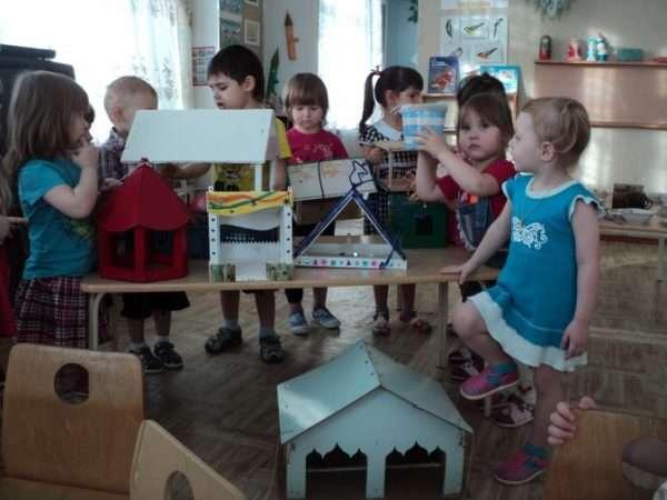 Дети около стола с кормушками-домиками