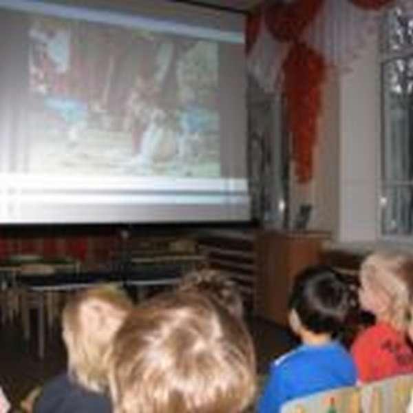 Дети смотрят мультфильм на большом экране