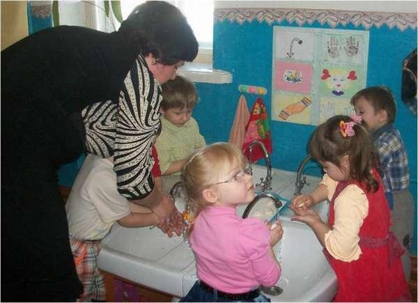 Дети моют руки, воспитательница помогает