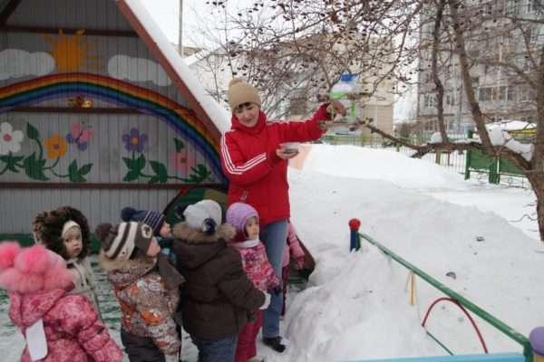 Воспитатель и дети рассматривают птичью кормушку на заснеженной площадке